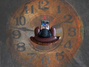 A person with a computer sitting inside a large clock